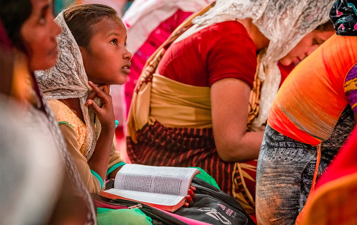 Girl reading bible in group of women