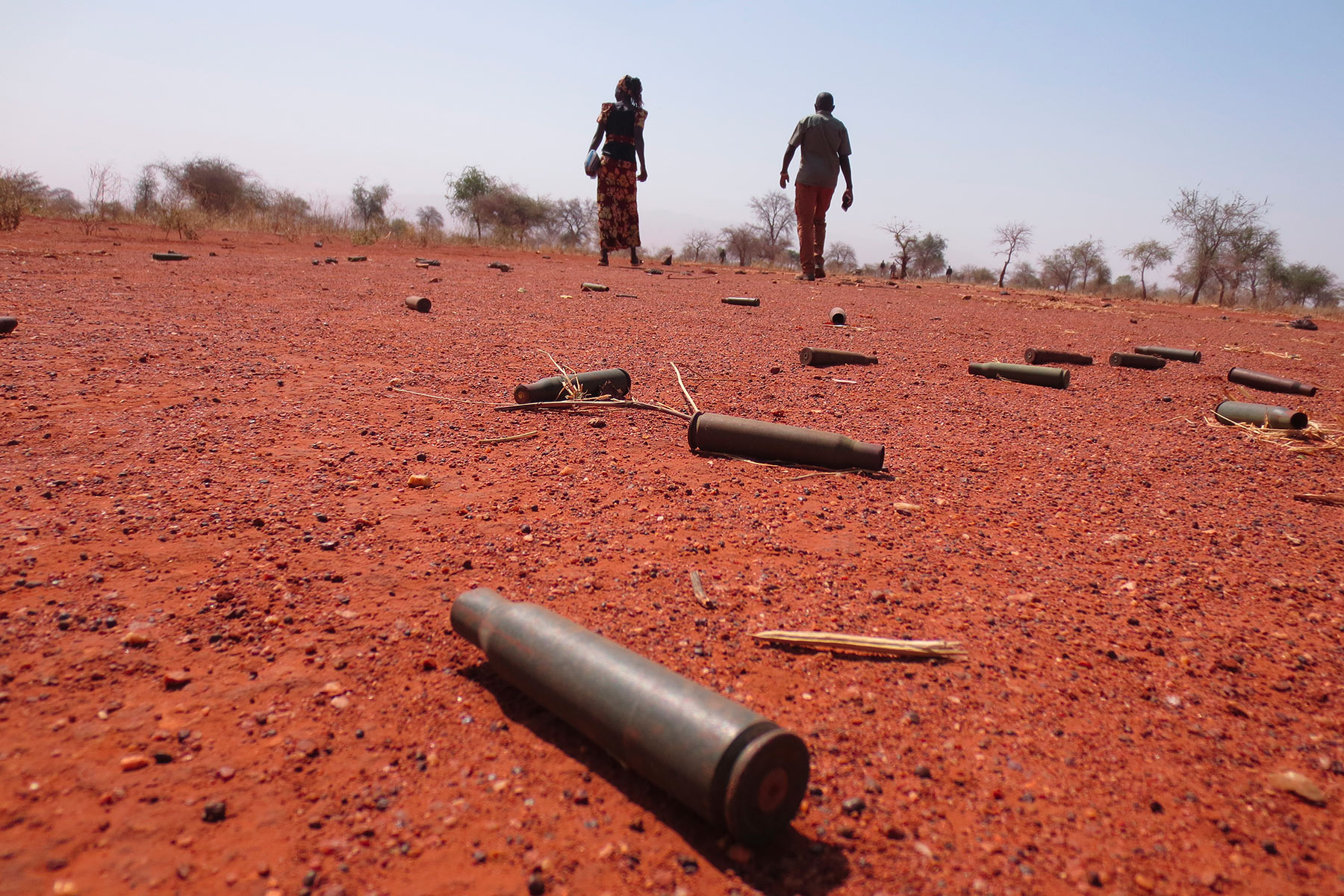 Two people walking across ground littered with bullet casings