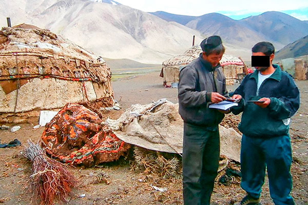 Two men reading a bible outside a yurt