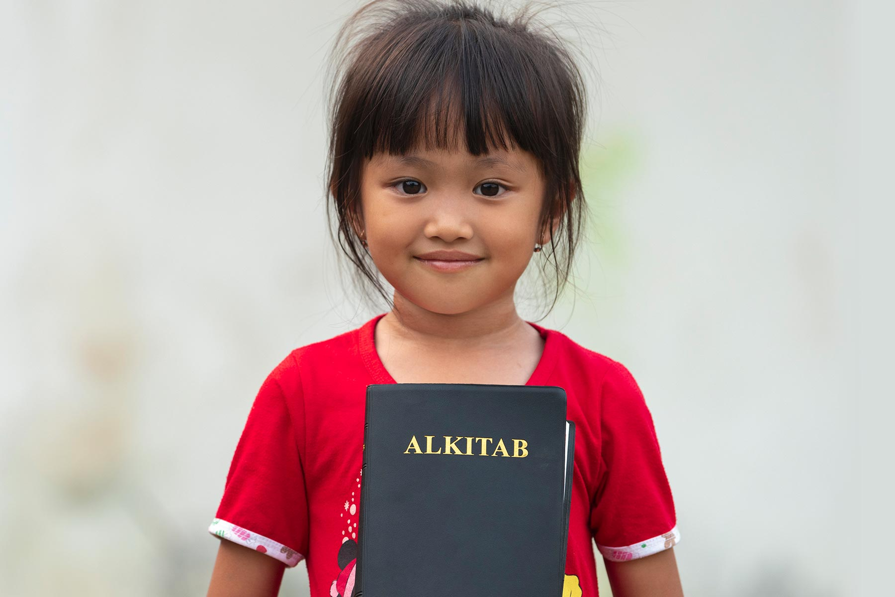 Smiling girl holding bible