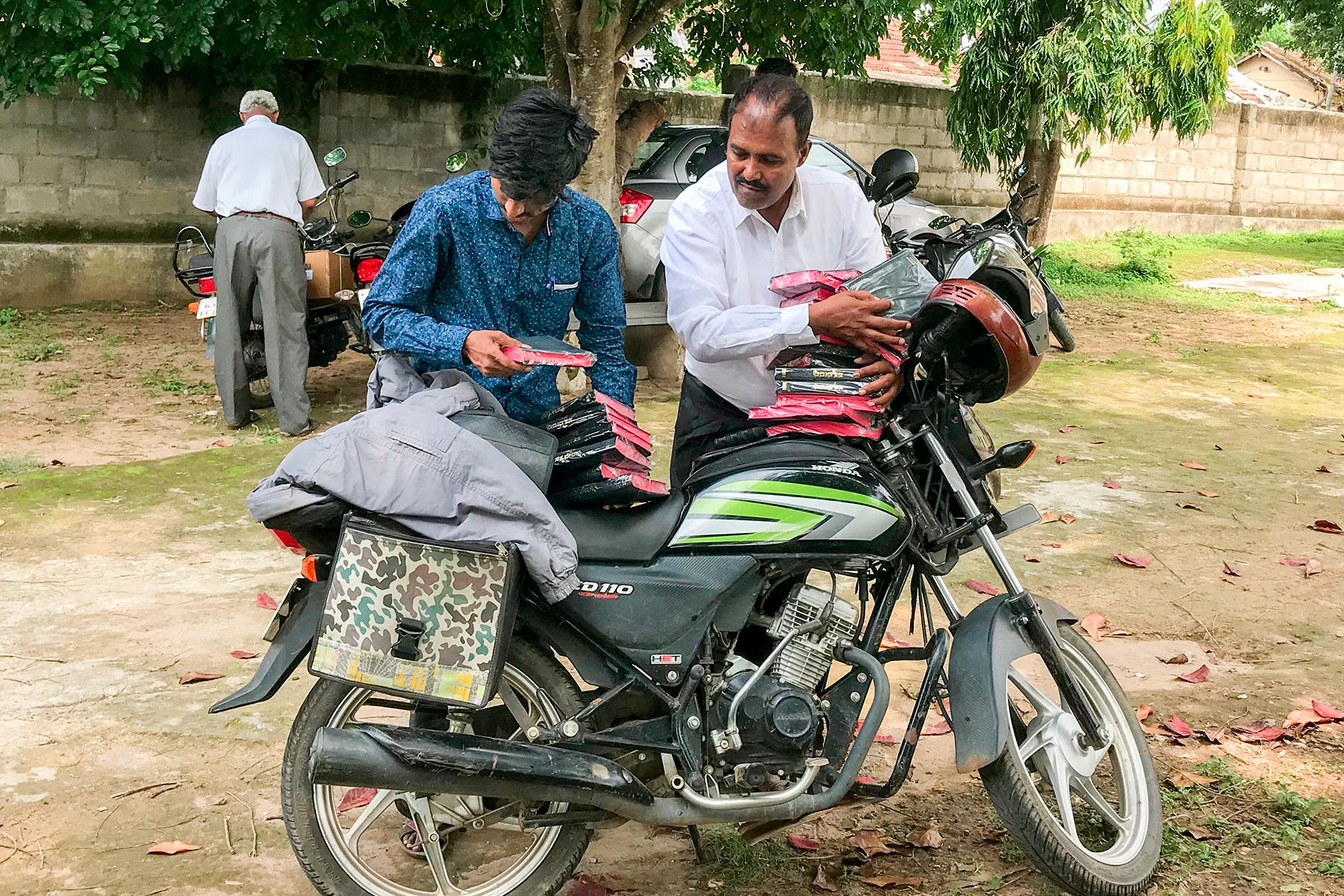 Men unloading bibles from motorcycle