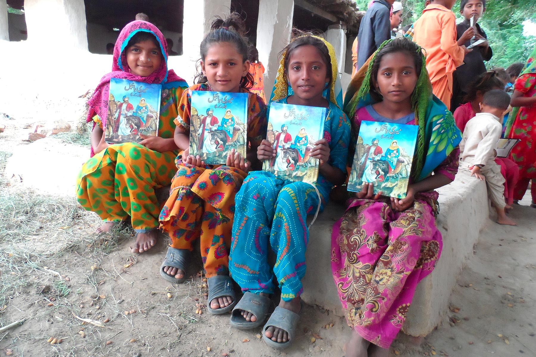 Four girls holding up books