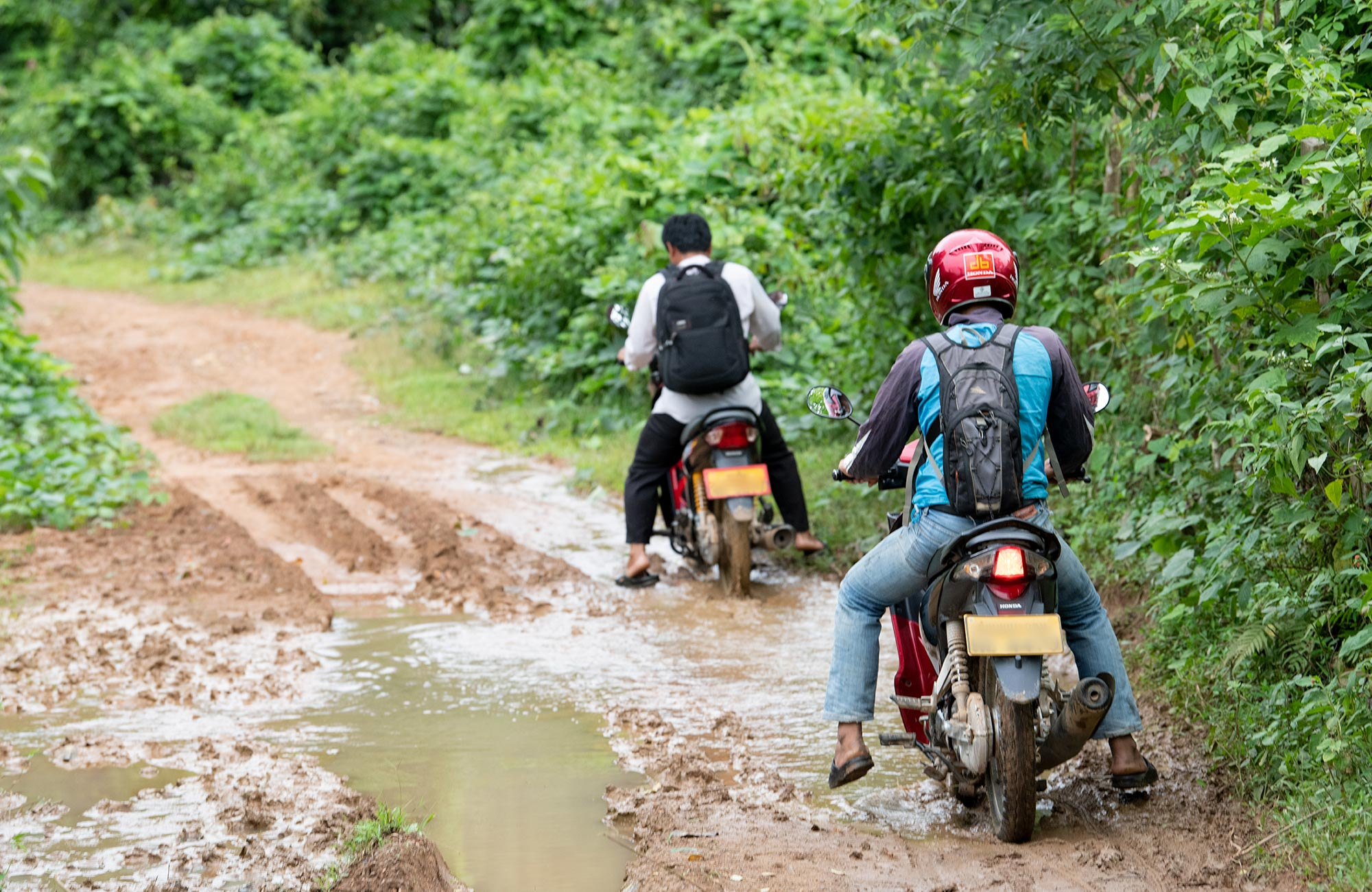 Two people driving motorcycles on muddy road in jungle
