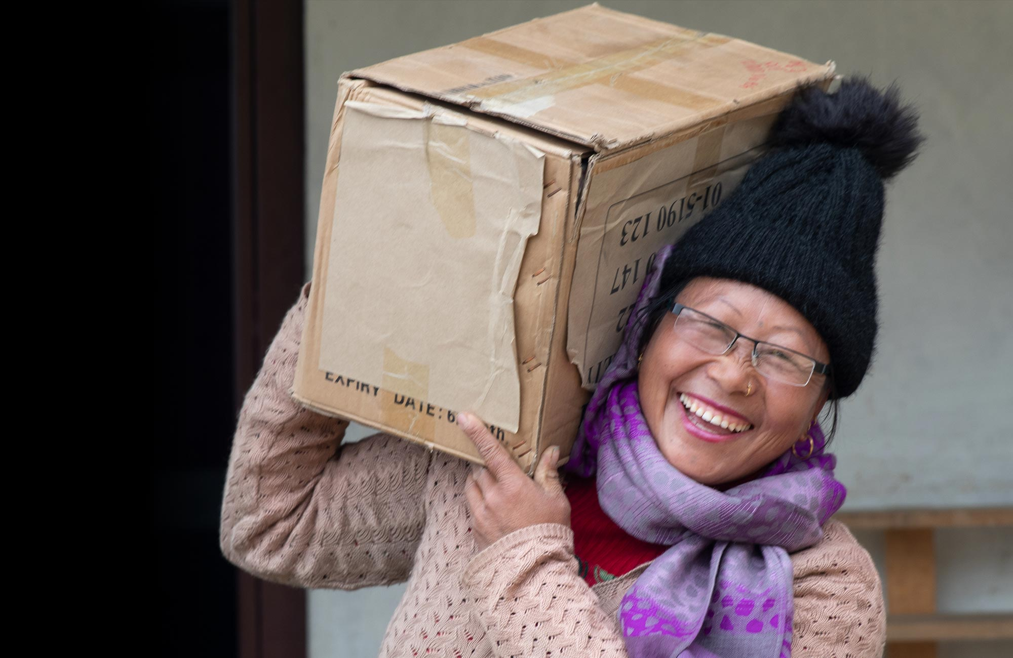 Smiling woman holding cardboad box