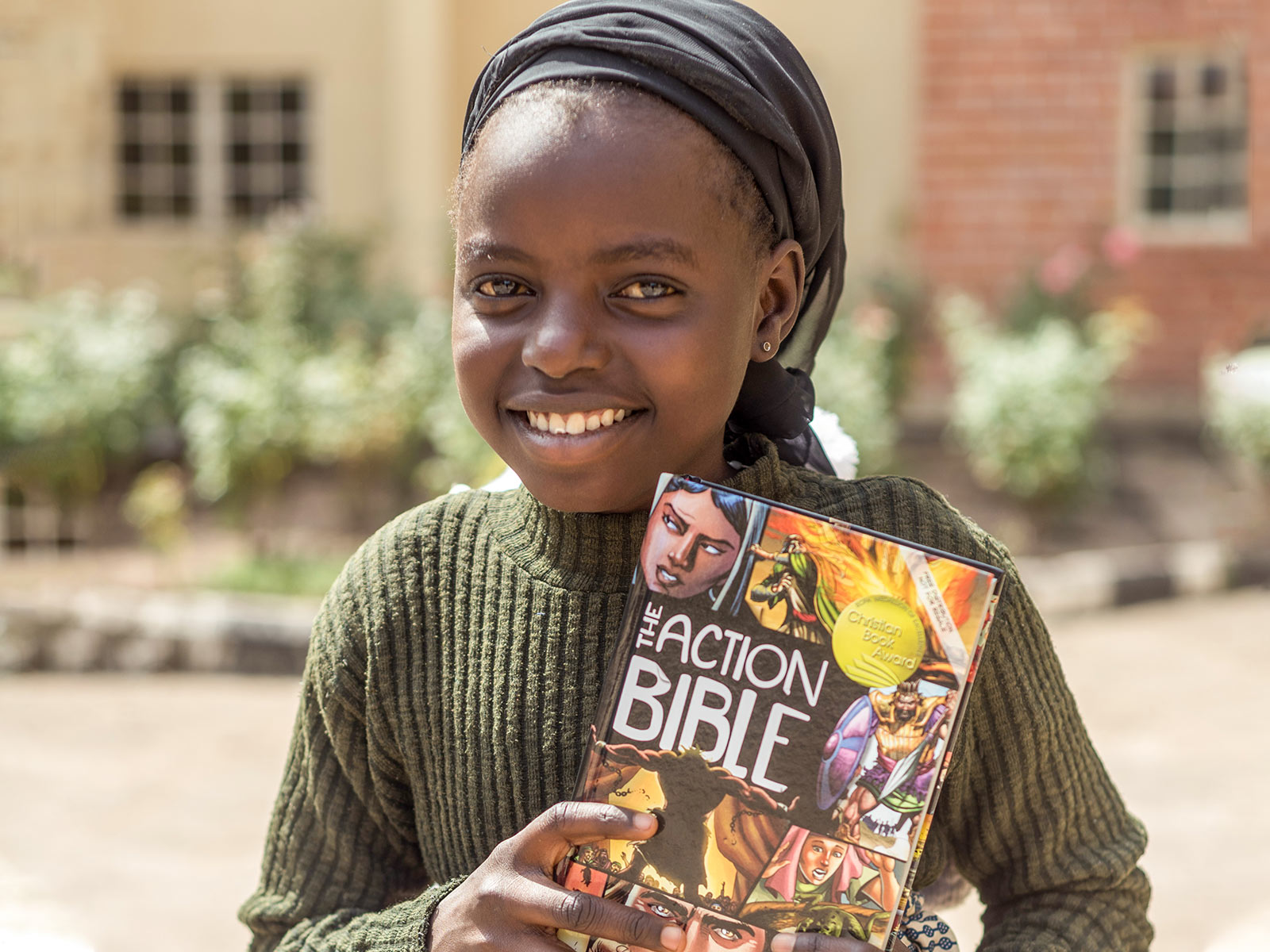 Smiling girl holding up action bible