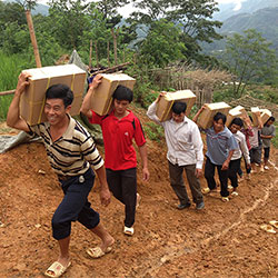 Men carrying crates of bibles up hill